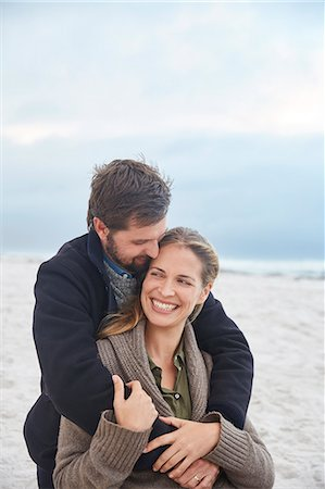 Smiling affectionate couple hugging on winter beach Stock Photo - Premium Royalty-Free, Code: 6124-08805279