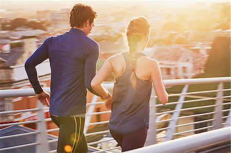 Runner couple running on sunny urban footbridge at sunrise Stock Photo - Premium Royalty-Free, Code: 6124-08820840