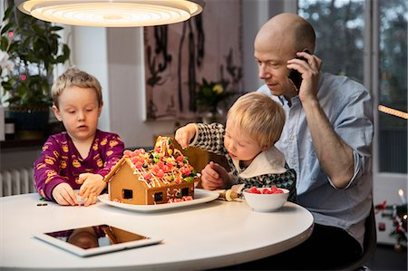 Sweden, Man and two boys (18-23 months, 4-5) decorating gingerbread house Stock Photo - Premium Royalty-Free, Code: 6126-08643201