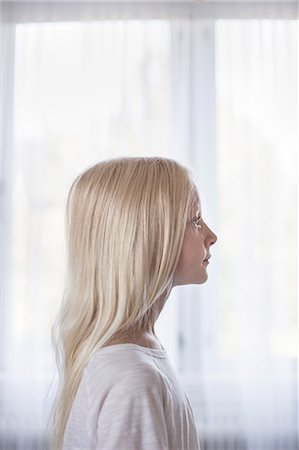 Sweden, Side view of blonde girl (10-11) in front of white curtains Stock Photo - Premium Royalty-Free, Code: 6126-08643887