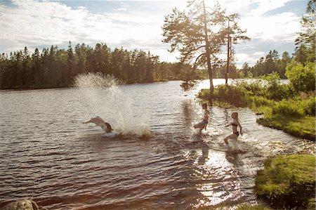 Sweden, Narke, Kilsbergen, Bjorktjarn, young man with children (10-11, 12-13) playing in lake at sunset Stock Photo - Premium Royalty-Free, Code: 6126-08643886