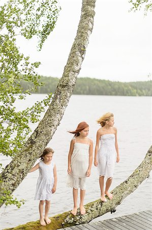 red hair preteen girl - Sweden, Vastmanland, Bergslagen, Hallefors, Sangshyttan, Three girls (4-5, 8-9, 10-11) standing on tree by lake Stock Photo - Premium Royalty-Free, Code: 6126-08643971