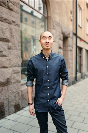 skinhead - Sweden, Sodermanland, Stockholm, Sodermalm, Smiling young man on sidewalk Stock Photo - Premium Royalty-Free, Code: 6126-08644046