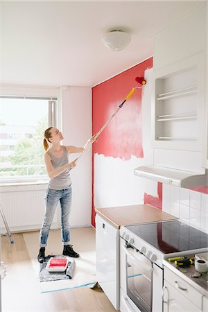 paint - Sweden, Woman painting wall in kitchen Stock Photo - Premium Royalty-Free, Code: 6126-08644063