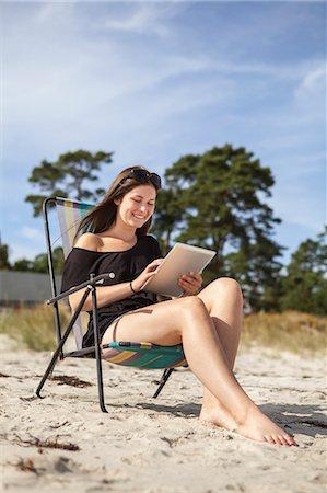 Sweden, Skane, Ahus, Teenage girl (16-17) using digital tablet on beach Stock Photo - Premium Royalty-Free, Code: 6126-08644082