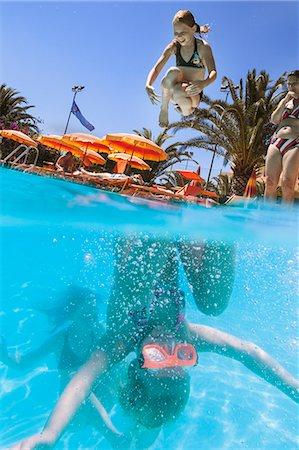 Italy, Sardinia, Alghero, Mother watching children (14-15, 16-17) diving into swimming pool Stock Photo - Premium Royalty-Free, Code: 6126-08644087