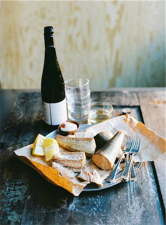 smoked - Sweden, Smoked fish, lemon, cutlery and bottle of wine on wooden table Stock Photo - Premium Royalty-Free, Code: 6126-08644325