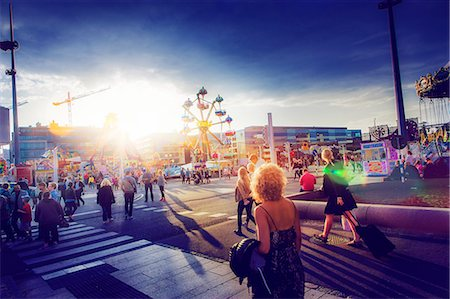 square - Sweden, Skane, Malmo, Anna Lindhs Plats, Woman crossing city street towards travelling carnival ground Stock Photo - Premium Royalty-Free, Code: 6126-08644499