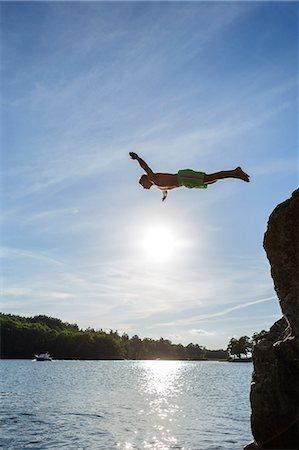 Sweden, Stockholm Archipelago, Teenage boy (16-17) jumping off cliff Stock Photo - Premium Royalty-Free, Code: 6126-08644616