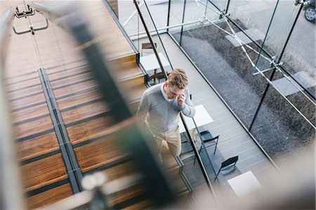 Finland, Young businessman walking downstairs and talking on phone Stock Photo - Premium Royalty-Free, Code: 6126-08644907