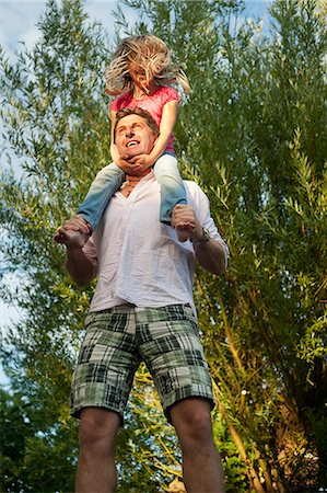 Sweden, Skane, Father carrying daughter (8-9) on shoulders Stock Photo - Premium Royalty-Free, Code: 6126-08658972