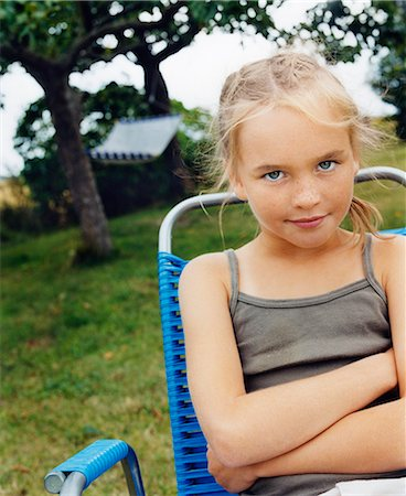 Sweden, Blonde girl (10-11) sitting in folding chair in garden Stock Photo - Premium Royalty-Free, Code: 6126-08658975