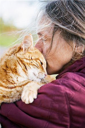 Sweden, Vastergotland, Fristad, Woman carrying and kissing cat Stock Photo - Premium Royalty-Free, Code: 6126-08659064