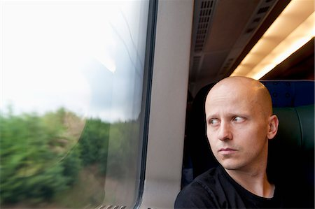 Sweden, Man looking through window on train Stock Photo - Premium Royalty-Free, Code: 6126-08659005
