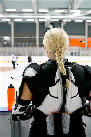 Sweden, Young ice hockey player standing by ice rink Stock Photo - Premium Royalty-Free, Code: 6126-08659037