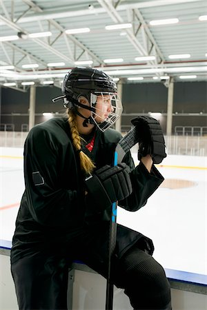 Sweden, Young ice hockey player sitting on ice rink boarding Stock Photo - Premium Royalty-Free, Code: 6126-08659036