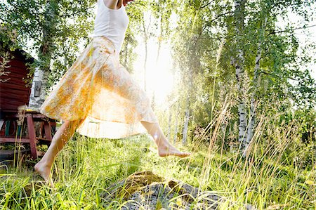 Sweden, Dalarna, Svardsjo, Young woman jumping in grass in backyard Stock Photo - Premium Royalty-Free, Code: 6126-08659144