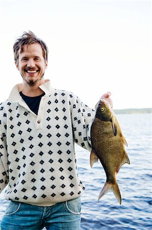 Sweden, Dalarna, Svardsjo, Smiling man holding caught fish by lake Stock Photo - Premium Royalty-Free, Code: 6126-08659138