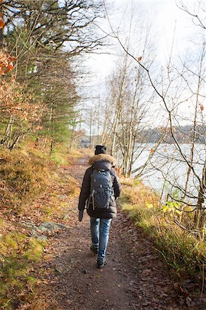 Sweden, Vastergotland, Lerum, Lake Aspen, Woman on footpath by lake Stock Photo - Premium Royalty-Free, Code: 6126-08659254