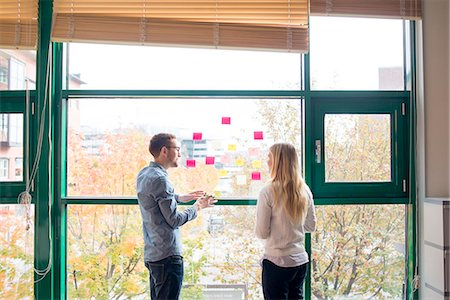 Sweden, Colleagues talking by window in office Stock Photo - Premium Royalty-Free, Code: 6126-08659372