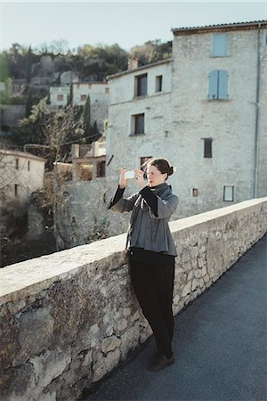 France, Languedoc-Roussillon, Sauve, Young woman photographing with smart phone Stock Photo - Premium Royalty-Free, Code: 6126-08659305