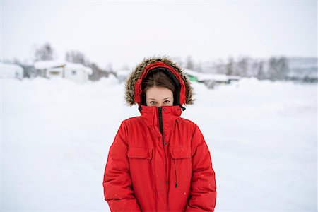 Sweden, Lapland, Hemavan, Portrait of young woman wearing red parka in winter Stock Photo - Premium Royalty-Free, Code: 6126-08659315