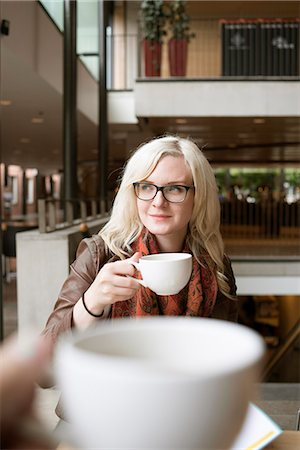 Sweden, Vastra Gotaland, Young blonde woman drinking coffee at campus cafeteria Stock Photo - Premium Royalty-Free, Code: 6126-08659335