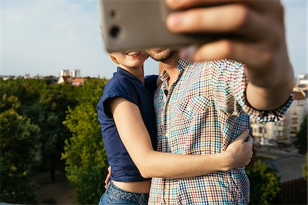 Germany, Berlin, Young couple hugging and taking selfie with smart phone Stock Photo - Premium Royalty-Free, Code: 6126-08659423