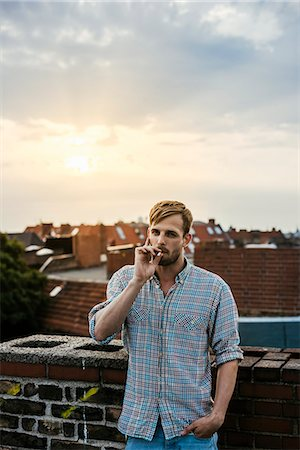 Germany, Berlin, Young blonde man smoking on rooftop at sunset Stock Photo - Premium Royalty-Free, Code: 6126-08659424