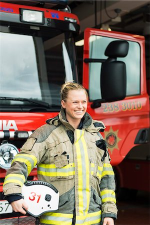 Sweden, Smiling female firefighter by fire engine Stock Photo - Premium Royalty-Free, Code: 6126-08635153