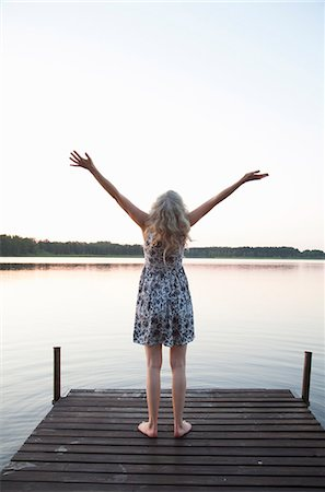 Sweden, Narke, Rear view of woman raising arms on jetty Stock Photo - Premium Royalty-Free, Code: 6126-08635194