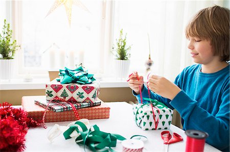 Boy (10-11) wrapping Christmas presents Stock Photo - Premium Royalty-Free, Code: 6126-08635196