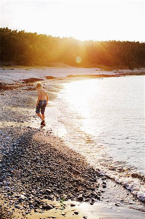 preteen boy shirtless - Sweden, Gotland, Lickershamn, Boy (8-9) walking on beach at sunset Stock Photo - Premium Royalty-Free, Code: 6126-08635277