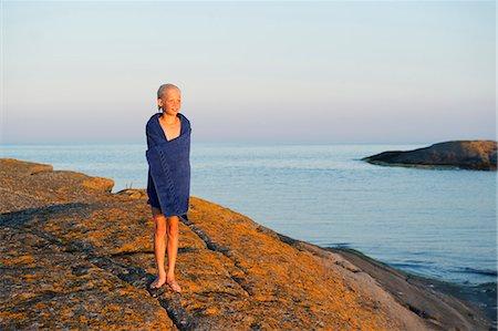 Sweden, Sodermanland, Stockholm Archipelago, Varmdo, Boy (12-13) wrapped in towel on rocky beach Stock Photo - Premium Royalty-Free, Code: 6126-08635302