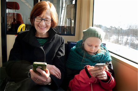 Sweden, Stockholm, Girl (10-11) with grandmother sitting in tram and using smart phones Stock Photo - Premium Royalty-Free, Code: 6126-08635498