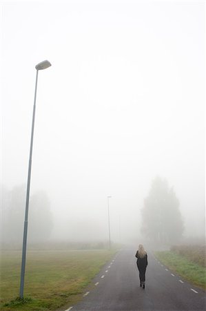 Sweden, Narke, Bjornhammaren, Woman walking along road in fog Stock Photo - Premium Royalty-Free, Code: 6126-08635561
