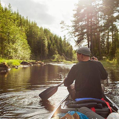Sweden, Vastmanland, Svartalven, Man paddling canoe along river Stock Photo - Premium Royalty-Free, Code: 6126-08635816
