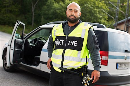 skinhead - Sweden, Sodermanland, Portrait of security guard with car in background Stock Photo - Premium Royalty-Free, Code: 6126-08635907