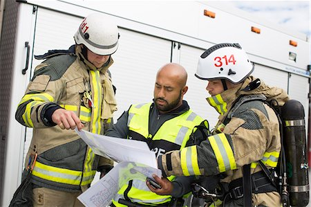 skinhead - Sweden, Sodermanland, Security guard and firefighters looking at plan Stock Photo - Premium Royalty-Free, Code: 6126-08635909