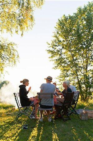 Sweden, Sodermanland, Jarna, Family having dinner in backyard at sunset Stock Photo - Premium Royalty-Free, Code: 6126-08635913