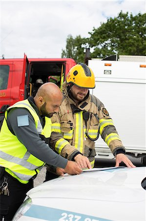 skinhead - Sweden, Sodermanland, Security guard and firefighter discussing plan Stock Photo - Premium Royalty-Free, Code: 6126-08635911