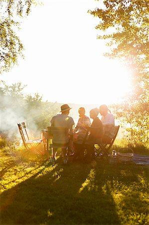 Sweden, Sodermanland, Jarna, Family having dinner in backyard at sunset Stock Photo - Premium Royalty-Free, Code: 6126-08635915
