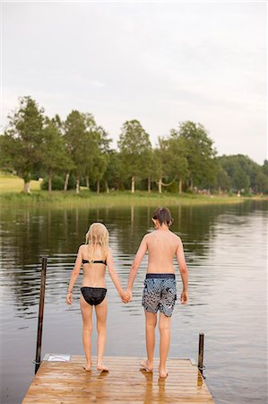 Sweden, Smaland, Braarpasjon, Girl (10-11) and boy (12-13) standing on edge of jetty Stock Photo - Premium Royalty-Free, Code: 6126-08636055