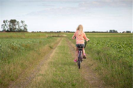 Sweden, Skane, Soderslatt, Beddinge, Blonde girl (10-11) riding bike along dirt road in green field Stock Photo - Premium Royalty-Free, Code: 6126-08636059