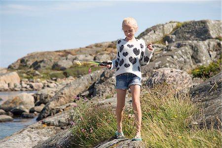 preteen thong - Sweden, Vastergotland, Lerum, Blonde girl (10-11) with fishing rod toy on rock Stock Photo - Premium Royalty-Free, Code: 6126-08636084