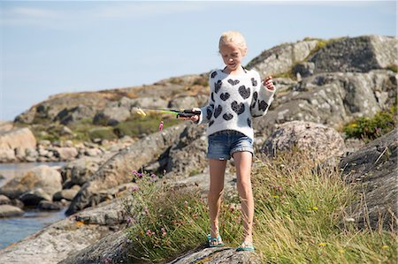 preteen thong - Sweden, Vastergotland, Lerum, Blonde girl (10-11) with fishing rod toy on rock Stock Photo - Premium Royalty-Free, Code: 6126-08636084