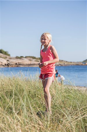 Sweden, Swedish West Coast, Halland, Kungsbackafjorden, Girl (10-11) standing in grass by sea Stock Photo - Premium Royalty-Free, Code: 6126-08636038