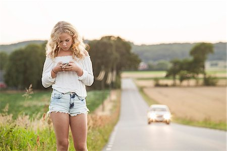 Sweden, Blekinge, Solvesborg, Teenage girl (14-15) with mobile phone standing at side of road Stock Photo - Premium Royalty-Free, Code: 6126-08636179