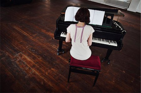 Sweden, Rear view of woman playing piano Stock Photo - Premium Royalty-Free, Code: 6126-08636127