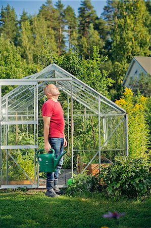 skinhead - Finland, Paijat-Hame, Heinola, Man standing outside greenhouse and holding watering can Stock Photo - Premium Royalty-Free, Code: 6126-08636523